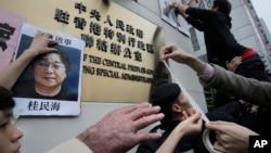 香港抗议者在北京驻香港机构中联办前贴上铜锣湾书店失踪老板桂民海的照片。 (2016年1月3日)
