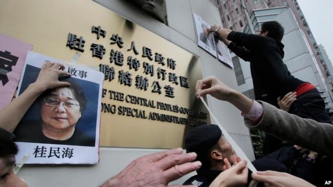 香港抗议者在北京驻香港机构中联办前贴上铜锣湾书店失踪老板 桂民海 的照片。 (2016年1月3日)