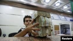 Pegawai pertukaran uang di Sana'a, Yaman, memegang setumpung uang Yaman.