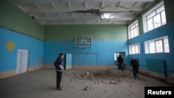 School coach Yuriy Balabanov meets his students inside a gym which was damaged by a recent shelling in Donetsk, eastern Ukraine, Oct. 19, 2014.