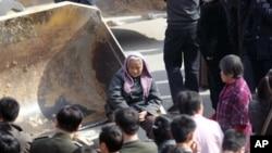 """从土改时的""""打土豪,分田地""""到如今有人戏称的""""打农民,占田地""""。图为2007年河南郑州一村庄的反拆迁村民坐在推土机前"""