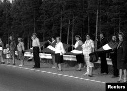 """Orang-orang bergandengan tangan dalam rantai manusia pada aksi """"Jalan Baltik"""" dekat Riga, Latvia, 23 Agustus 1989."""