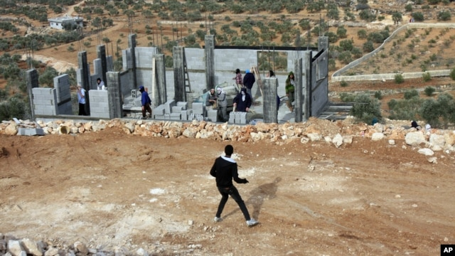 Palestinians throw stones at Israeli settlers who are later detained by Palestinian villagers in a building under construction near the West Bank village of Qusra, southeast of the city of Nablus, Jan. 7, 2014.