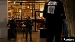 Israeli policemen secure the entrance to a restaurant following a shooting attack in the center of Tel Aviv, June 8, 2016.
