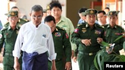 FILE - Rakhine Chief Minister Nyi Pu, left, and Myanmar's high ranking military officers return from a trip with a diplomatic mission and United Nations officials to the Maungdaw area in northern Rakhine State in Myanmar, Nov. 3, 2016.