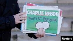 El primer ministro francés, Manuel Valls, sostiene una copia de Charlie Hebdo al salir del Palacio de los Eliseos, en París.