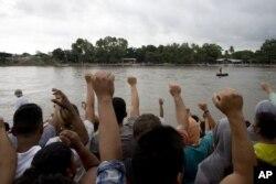 Migrantes hondureños cantan su himno nacional en la orilla del río Suchiate, en la frontera entre Guatemala y México, en Tecún Umán, Guatemala, el 18 de octubre de 2018.