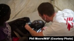 A Médecins Sans Frontières (MSF) doctor treats a girl who suffered an electric shock, at the MSF clinic set up at the camp for displaced people in the grounds of the United Nations Mission to South Sudan (UNMISS) base in Juba, South Sudan, on January 12,