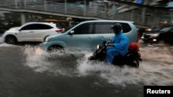 People ride motorcycles through a flooded street in a business district in Jakarta, Indonesia, Dec. 11, 2017.