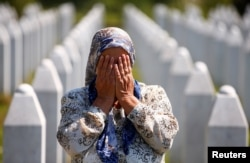 A woman prays at a graveyard, ahead of a mass funeral in Potocari near Srebrenica, Bosnia and Herzegovina July 11, 2020. Bosnia marks the 25th anniversary of the massacre of more than 8,000 Bosnian Muslim men and boys, with many relatives unable to attend
