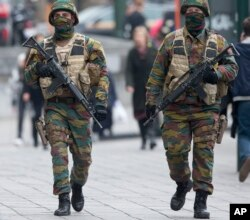 FILE - Belgian soldiers patrol outside a court building where Salah Abdeslam, the top suspect in last year's deadly Paris attacks, was expected to appear before a judge in Brussels, Belgium, March 24, 2016.