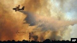 19일 산불 진화 작업이 계속되고 있는 포르투갈 중부 지역에서 소방 비행기가 물을 뿌리고 있다.