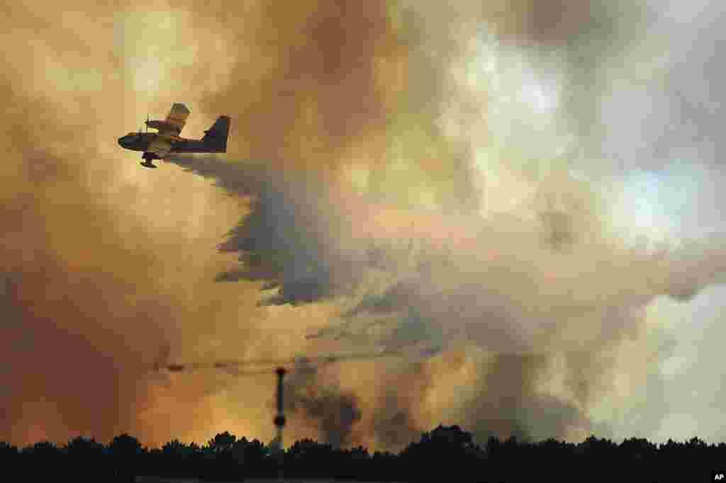 A fire fighting aircraft drops water over a fire outside the village of Pedrogao Grande central Portugal. . More than 2,000 firefighters battled to contain major wildfires in the central region of the country, where one blaze killed dozens of people.