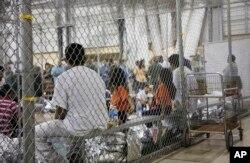 En esta foto proporcionada por la agencia de Aduanas y Protección Fronteriza de EE.UU., personas que han sido detenidas por entrada ilegal a Estados Unidos, permanecen en una de las jaulas de una instalación en McAllen, Texas, el domingo 17 de junio de 2018.