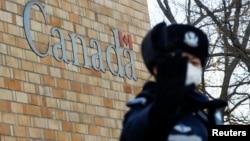 在加拿大驻北京大使馆外一名中国警察向摄影记者打手势。(2018年12月12日)