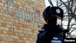 在加拿大駐北京大使館外一名中國警察向攝影記者打禁止的手勢。 (2018年12月12日)