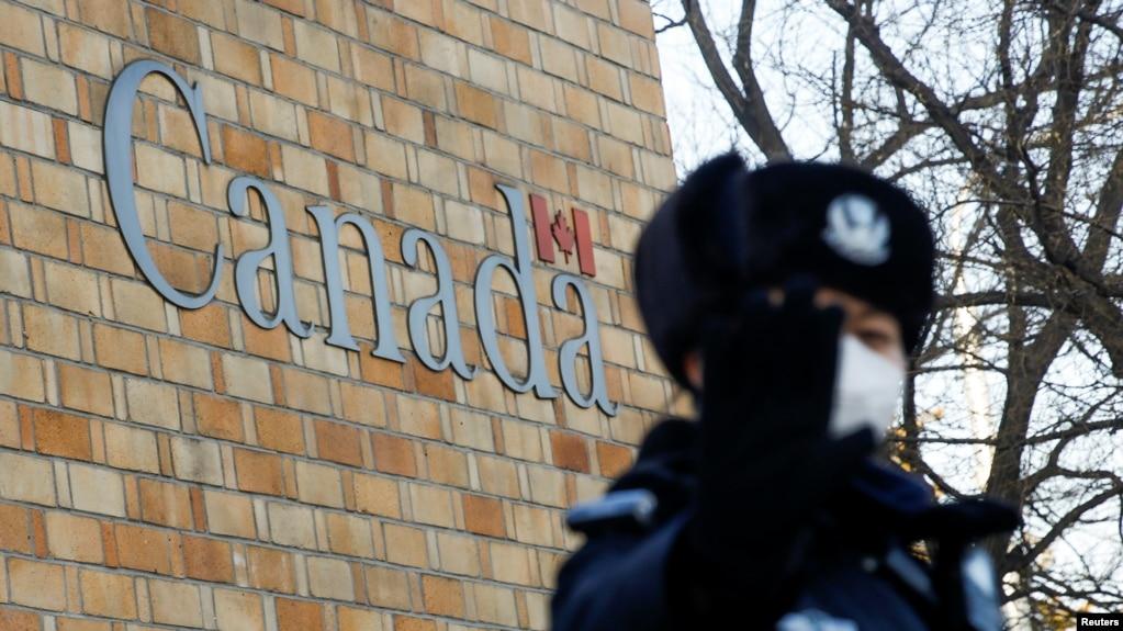在加拿大驻北京大使馆外一名中国警察向摄影记者打禁止的手势。(2018年12月12日)