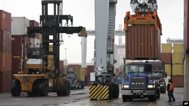 Driver watches as a freight container is lowered onto a tractor trailer by crane, Port of Boston, Dec. 18, 2012.