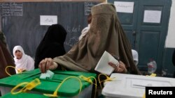 A woman casts her ballot at a polling station in Peshawar May 11, 2013.