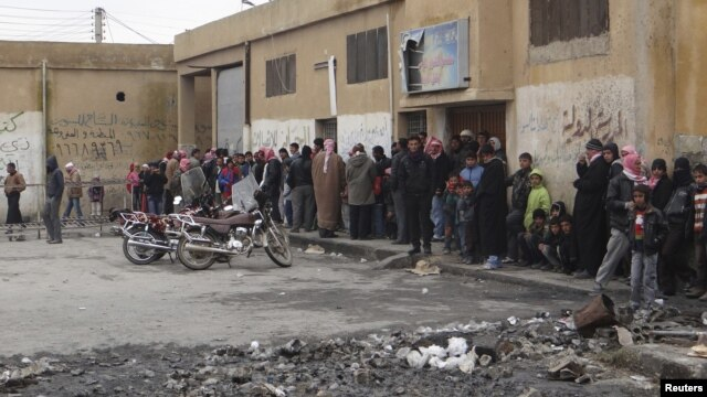 People queue to buy bread at a local bakery at Tel Abyed near Hasaka, December 17, 2012.