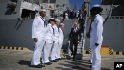 Ukrainian Prime Minister Arseniy Yatsenyuk, center, leaves the USS Donald Cook, the Navy's newest missile cruiser, and passes by the guard of honor in Odessa, Ukraine, Sept. 1, 2015.