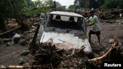 Cư dân cạnh chiếc xe bị hư hại vì bão tại thị trấn Arayat, Pampanga, miền bắc Philippines, ngày 13/10/2013.