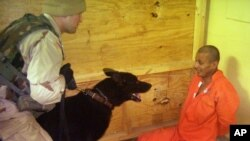 This image obtained by The Associated Press shows Sgt. Michael Smith, left, with his dog, watching a detainee at an unspecified date in 2003 at the Abu Ghraib prison in Baghdad, Iraq.