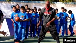 FILE - Lamar Odom of NBA basketball team Los Angeles Clippers shows a group of children how to pass the ball during a coaching clinic at the Huangzhuang School in Beijing, China, Oct. 10, 2012.