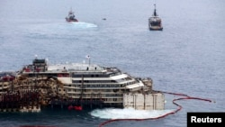 Các công nhân nâng chiếc du thuyền Costa Concordia lên tại cảng Giglio, ngày 14/7/2014.