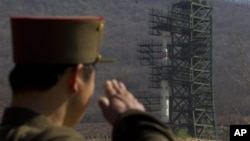 Binh sĩ Triều Tiên phía trước hỏa tiễn Unha-3 tại cơ sở vệ tinh Sohae ở Tongchang-ri.