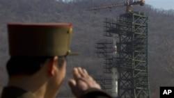在這張攝於4月8日文件的照片中,一名北韓士兵在北韓的一個衛星發射中心的火箭旁邊站崗