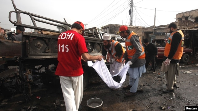 Rescue workers collect body parts after a bomb attack at Fauji Market in Peshawar, December 17, 2012.