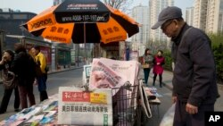 A man looks at a newsstand with a copy of the day's Global Times displayed on a basket in Beijing, China, Tuesday, April 5, 2016.