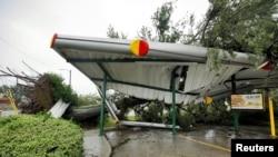 Oboreno stablo leži na srušenom krovu jednog restorana brze hrane u Vilmingtonu u Severnoj Karolini.