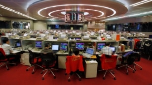 Floor traders work at the Hong Kong Stock Exchange. Investors in Hong Kong will be able to trade stocks on the Shanghai stock exchange.