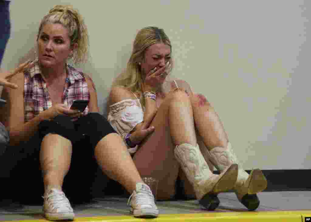 A woman cries while hiding inside the Sands Corporation plane hangar after a mass shooting in which dozens were killed at the Route 91 Harvest country festival, Oct. 1, 2017, in Las Vegas, Nevada.