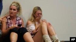 Seorang perempuan menangis saat bersembunyi di hangar pesawat Sands Corporation setelah penembakan massal yang menewaskan puluhan orang di Route 91 Harvest country festival, 1 Oktober 2017, di Las Vegas.
