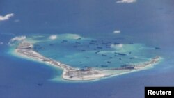 Chinese dredging vessels are purportedly seen in the waters around Mischief Reef in the disputed Spratly Islands in the South China Sea in this still image from video taken by a P-8A Poseidon surveillance aircraft provided by the United States Navy, May 2