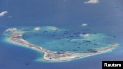 Chinese dredging vessels are seen in the waters around Mischief Reef in the disputed Spratly Islands in the South China Sea. This is a still image from video taken by a P-8A Poseidon surveillance aircraft provided by the United States Navy, May 21, 2015. (REUTERS/U.S. Navy/Handout via Reuters)