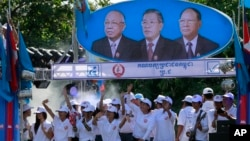 Supporters of Prime Minister Hun Sen's Cambodian People's Party dance under portraits of the party leaders, from left, Chea Sim, Hun Sen and Heng Samrin, during an election campaign in Phnom Penh, Cambodia, Thursday, June 27, 2013.