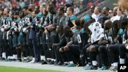 Jacksonville Jaguars players lock arms and kneel down during the playing of the U.S. national anthem before an NFL football game against the Baltimore Ravens at Wembley Stadium in London, Britain, Sept. 24, 2017.