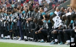 Jacksonville Jaguars players lock arms and kneel down during the playing of the U.S. national anthem before an NFL football game against the Baltimore Ravens at Wembley Stadium in London, Sept. 24, 2017.