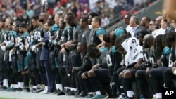 杰克逊维尔美洲虎和巴尔的摩乌鸦队比赛前,美洲虎队的球员在播放国歌期间手挽手,有人坐着,有人站立。乌鸦队球员也是有人站立,有人坐着,互相挽着臂膀。(2017年9月24日)