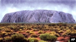 Ayers Rock (Uluru) takes on an unusual color as waterfalls cascade down its' walls in central Australia, Tuesday February 22, 2000 following the worst floods in the area for two decades. The rock which is usually a reddish colour is seldom seen like this.