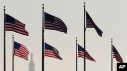FILE - Bendera Amerika Serikat dengan latar belakang Gedung Capitol Hill, Washington DC. DPR Amerika telah meloloskan anggaran untuk mendanai pemerintah sampai September mendatang.