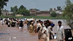 Evacuating residents carry their belongings through floodwaters the Mohib Bhanda area in Nowshera district, Pakistan, 31 Jul 2010