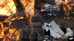 A statue stands outside a burning house in Ein Hod, northern Israel, 04 Dec 2010