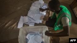 Seorang petugas tempat pemungutan suara menghitung kertas suara di sebuah tempat pemungutan suara di Lome pada 22 Februari 2020 selama putaran pertama Pemilihan Presiden Togo. (Foto: AFP/Yanick Folly)