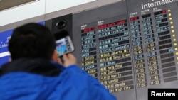 Seorang pengunjung memotret papan informasi jadwal kedatangan pesawat Malaysia Airlines dengan nomor penerbangan MH370 (atas, berwarna merah) di Bandara Internasional Beijing, 8 Maret 2014.