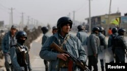 FILE - Afghan policemen keep watch at the site of clashes with protesters in Kabul, Jan. 31, 2015.